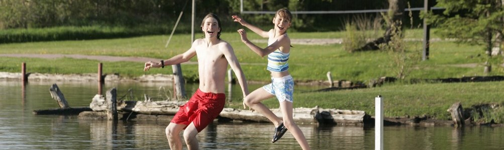 Two smiling young adults jumping off a dock into  a lake on a sunny day