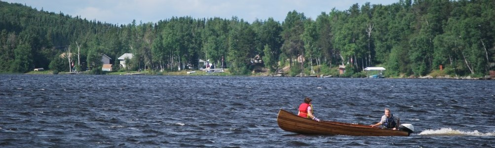 A couple in a canoe on a peaceful lake surrounded by conifers