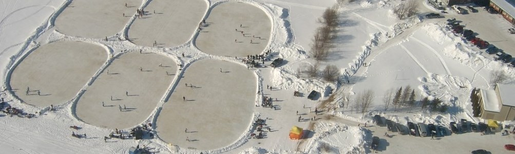 Aerial view of outdoor skating rinks, surrounded by snowy banks