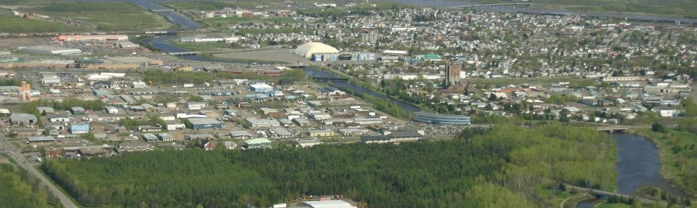 Aerial view of the City of Thunder Bay, views of buildings, conifers, and a river winding through the city