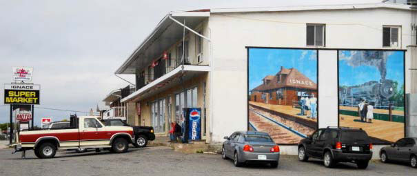 Tow murals showing a railroad scene painted on the side of a supermarket