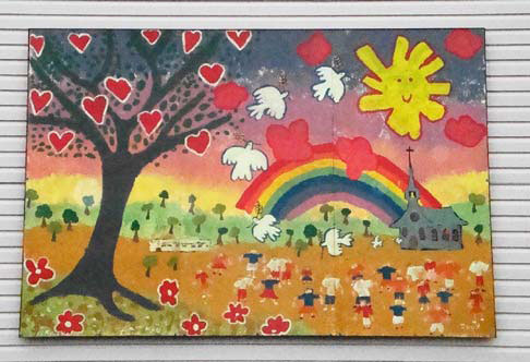 Colourful child's painting, with a smiling sun, a rainbow, a church, and a tree with red heart-shaped leaves
