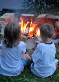 Two kids sitting at a campfire, roasting marshmallows