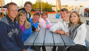 Group of kids sitting at a picnic table, smiling